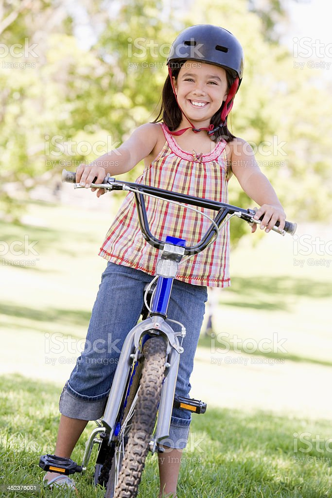 Young girl on bicycle outdoors smiling royalty-free stock photo