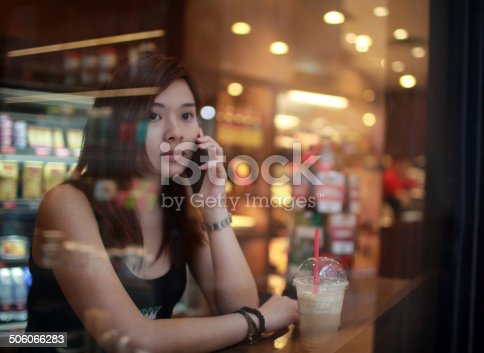 istock Young girl on call looking out behind the cafe window 506066283