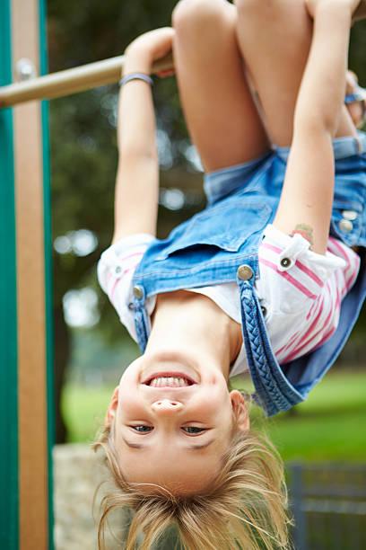 young girl on climbing frame in playground - schommelen bungelen stockfoto's en -beelden