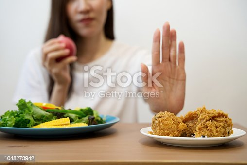 istock Young girl on dieting for good health concept. Close up female using hand reject junk food by pushing out her favorite fried chicken and choose red apple and salad for good health. 1048273942