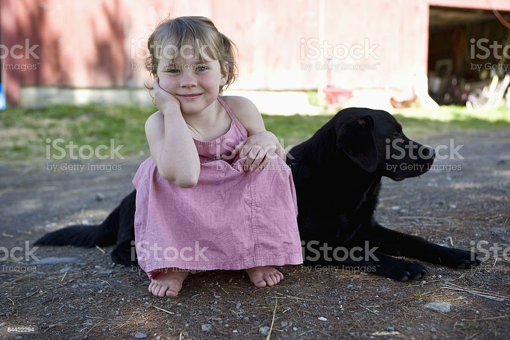 Young girl on farm sitting with her dog royalty-free stock photo