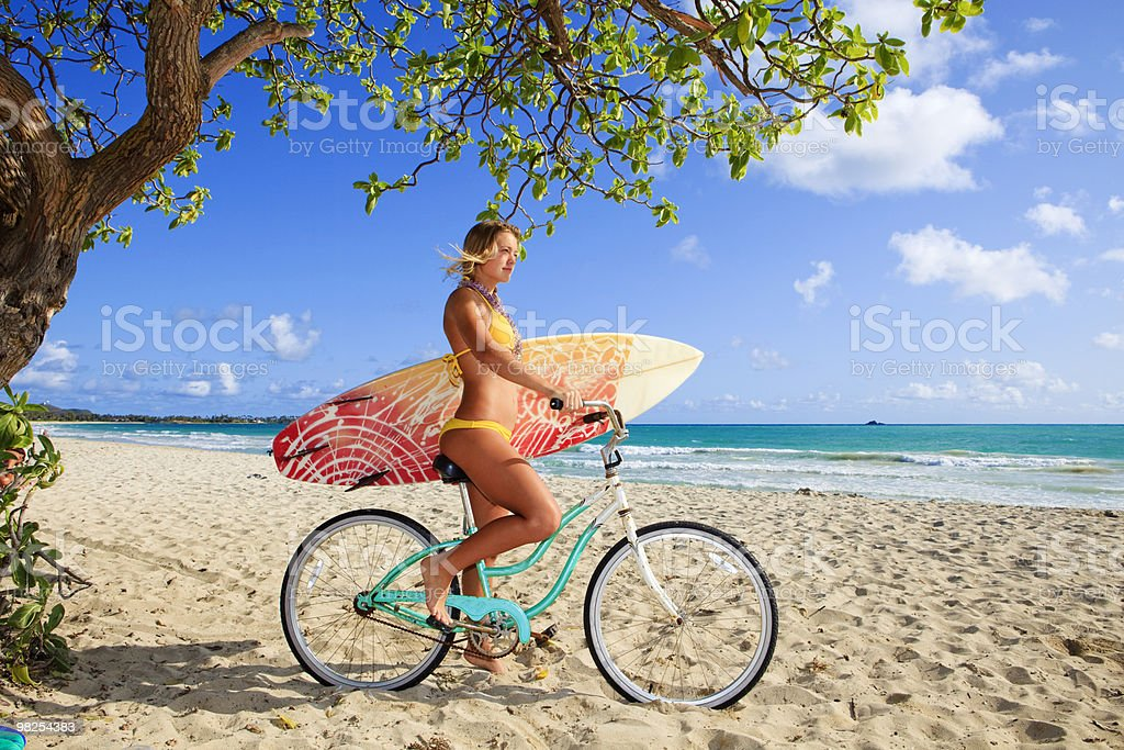 young girl on her bicycle with surfboard stock photo