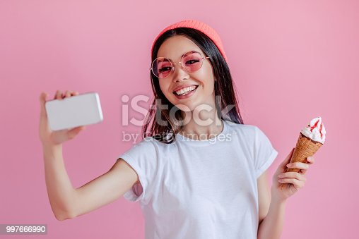 Young asian teenage girl isolated on pink background. Stylish young woman with ice cream is making selfie on a smart phone.
