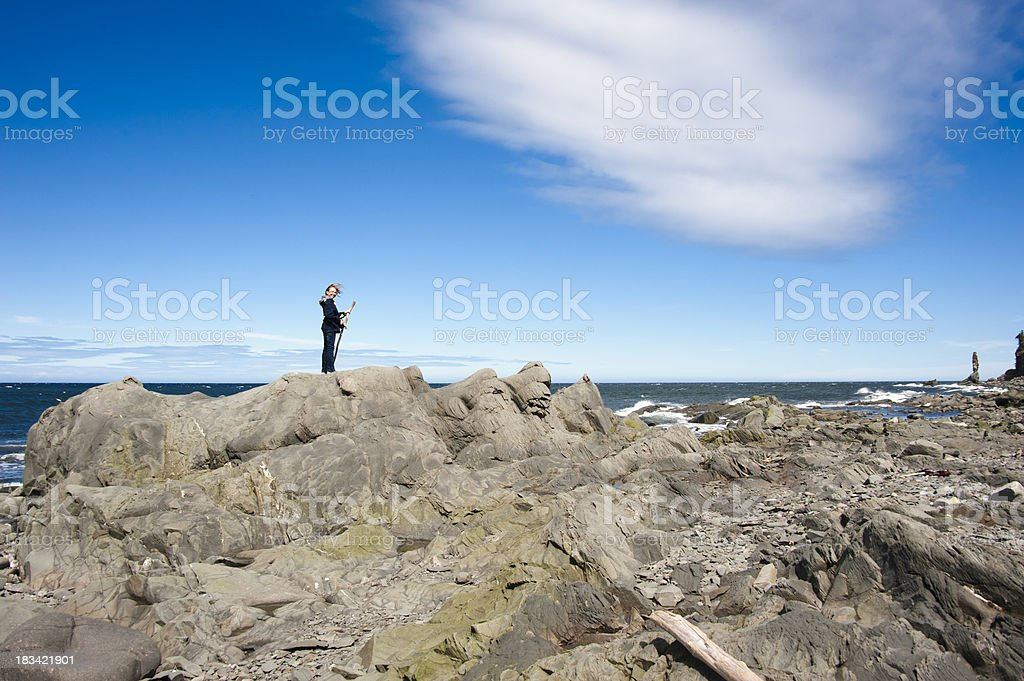 Young girl on rock formation. stock photo