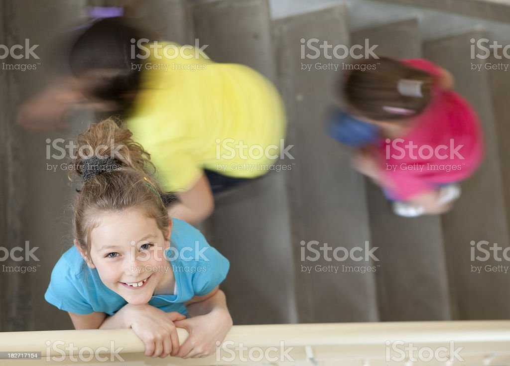 young girl on stairs in her school stock photo