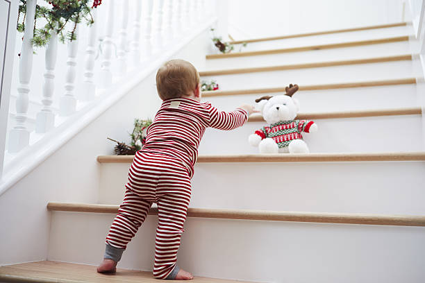 young girl on stairs in pajamas at christmas - christmas tree stockfoto's en -beelden