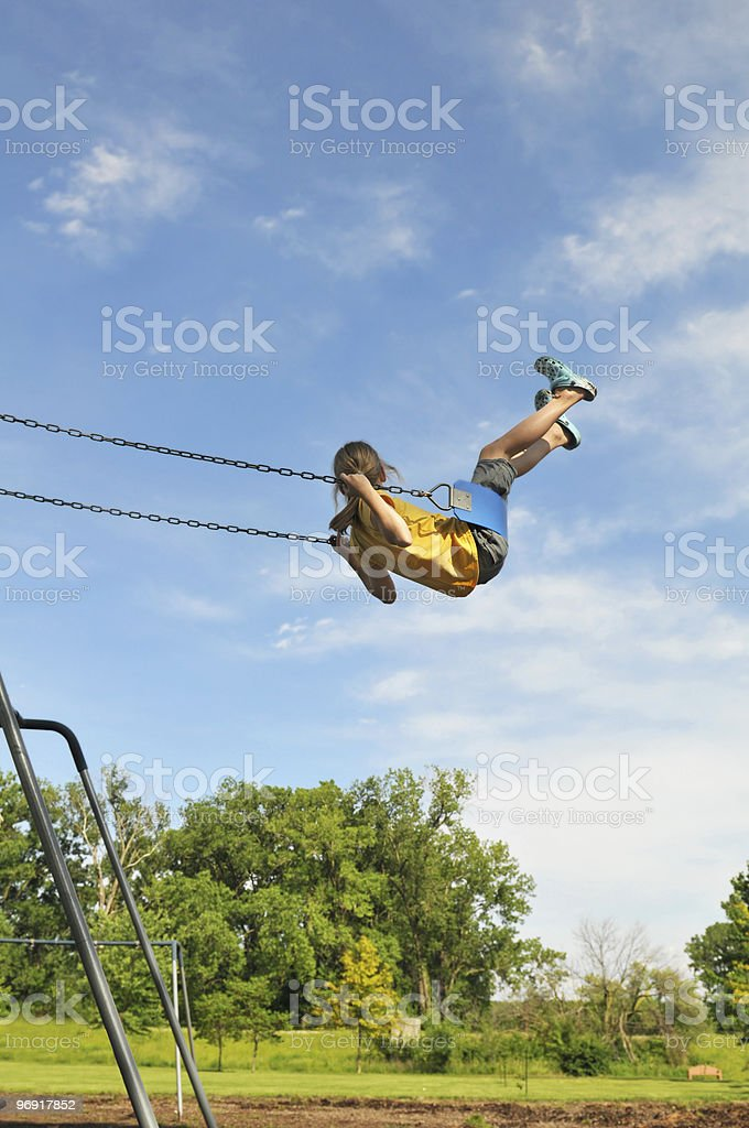Young girl on swing against a blue sky royalty-free stock photo