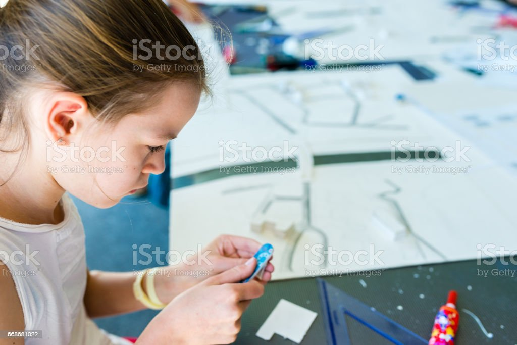 Young girl on the course of architectural design for children - preparing architectural model stock photo