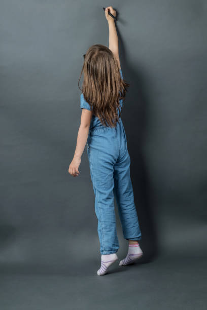 young girl on tiptoe writing at grey background stock photo