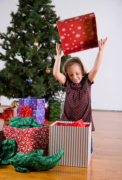 Young girl opens gift stock photo