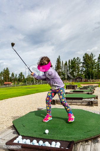 Swedish young girl outdoors at a driving range playing golf and practice her swing. Vertical composition.