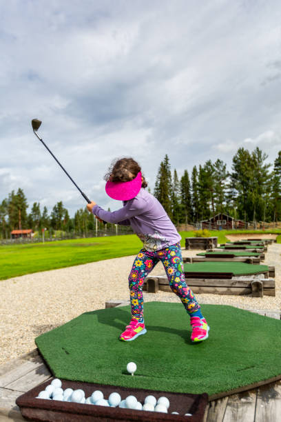Young girl outdoors at a driving range playing golf and practice her swing. stock photo
