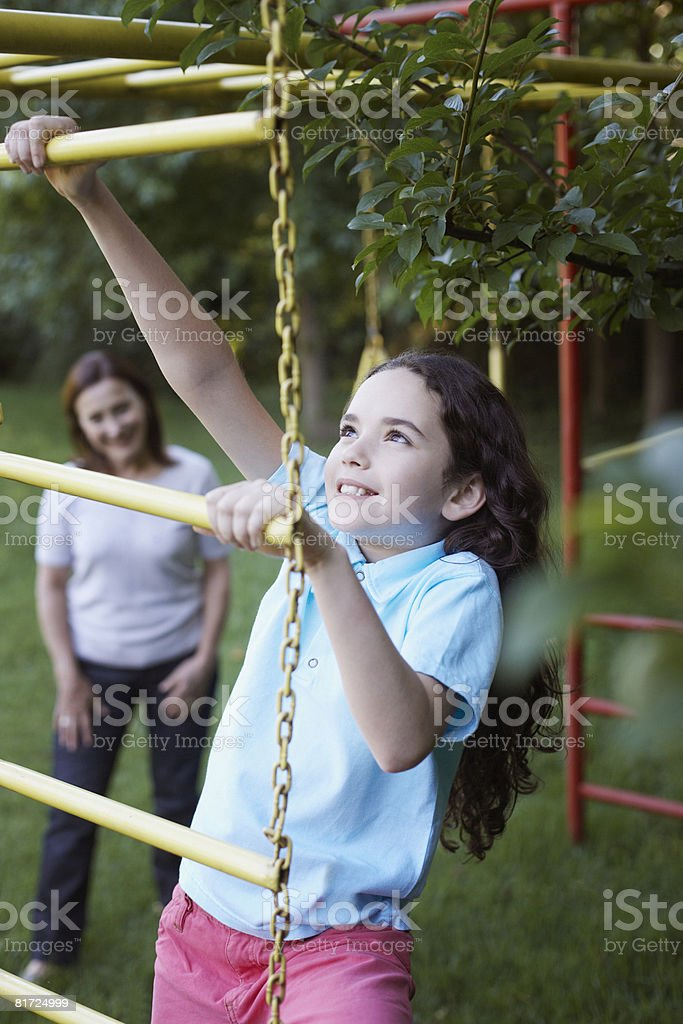Young girl outdoors at playground climbing with senior woman in background royalty-free stock photo