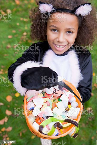 Young girl outdoors in cat costume on halloween holding candy picture id160135304?b=1&k=6&m=160135304&s=612x612&h=ehnhm3fxcv6p1xffxi1paq seldkrvavu xtl2vakg0=