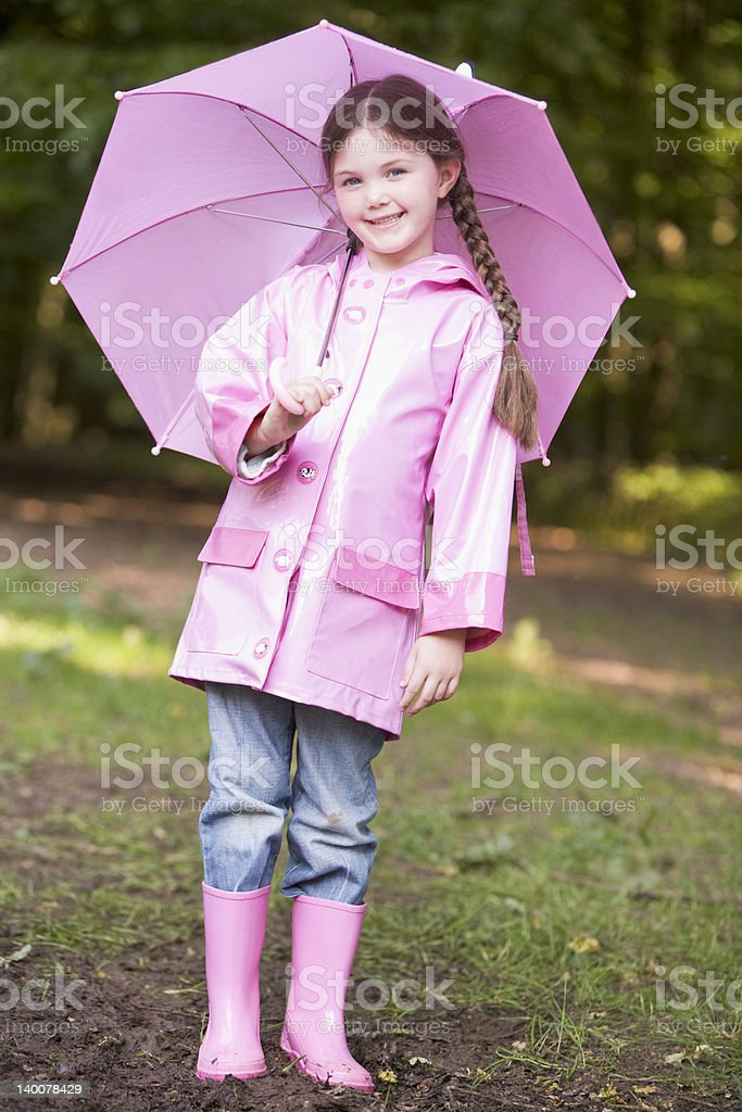 Young girl outdoors with umbrella smiling royalty-free stock photo