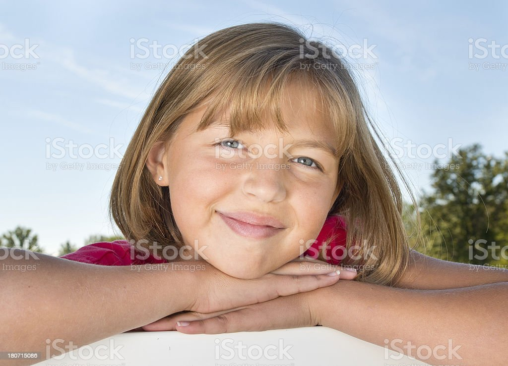 Young girl outside lleaning on fence royalty-free stock photo