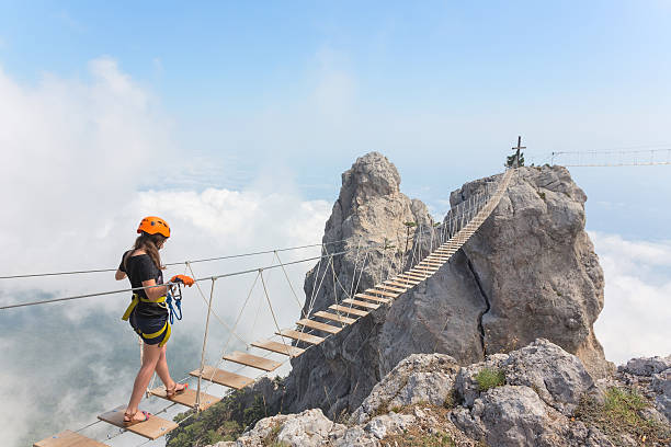 Young girl over abyss Young woman crossing the chasm on the rope bridge ravine stock pictures, royalty-free photos & images