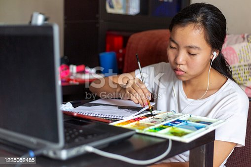 655303558 istock photo young girl painting in the living room 1225052485