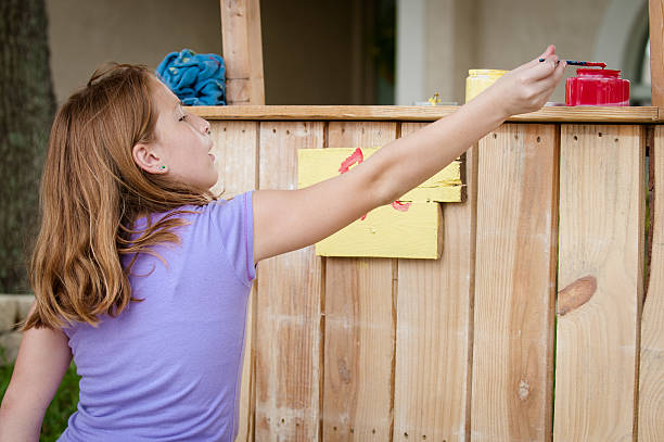 Young girl painting lemonade stand sign stock photo