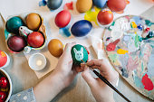 Close up of girl's hands painting on Easter egg