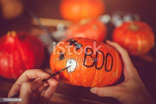 Woman painting on pumpkin preparing to Halloween in autumn