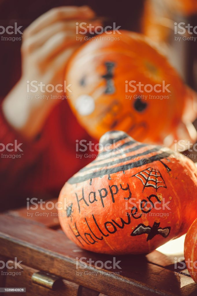 Young girl painting on pumpkin in Halloween stock photo