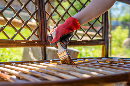 Young girl painting wooden exotic wood bench in the garden with a brush. Close up