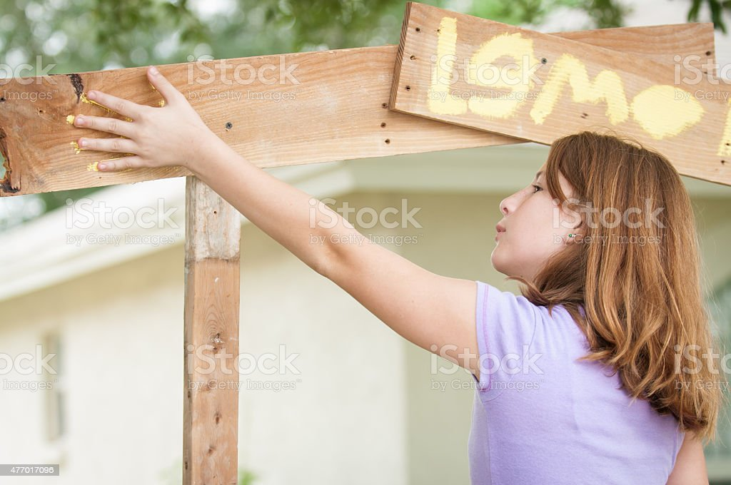 Young girl paintng lemonade stand stock photo