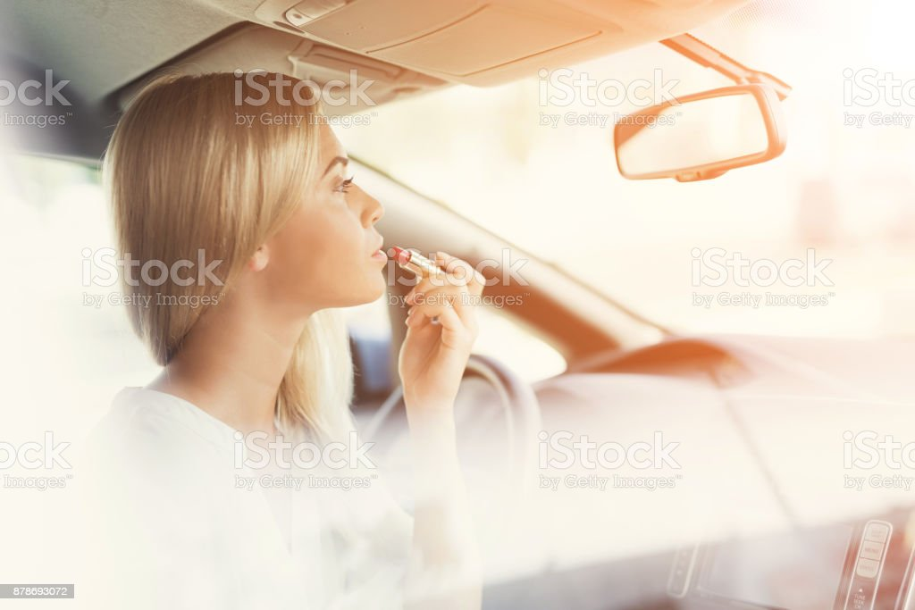 A young girl paints her lips while sitting at the wheel of an electric car. stock photo