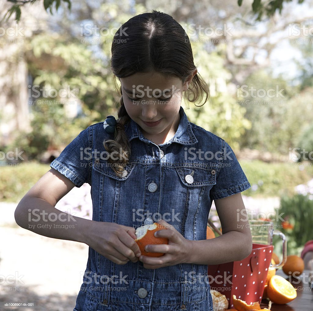 Young girl (8-9) peeling orange in garden 免版稅 stock photo
