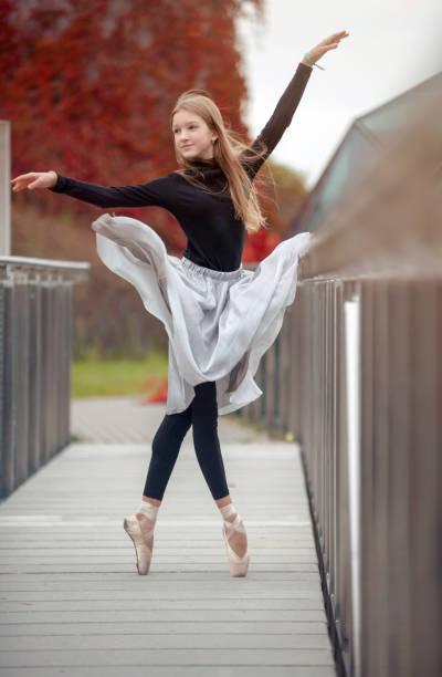 Junge Mädchen führt Ballettpositionen auf der Brücke – Foto