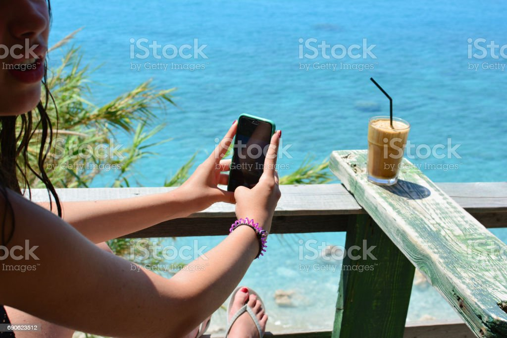 Young girl photographing ice coffee stock photo