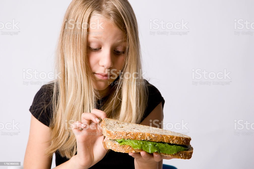 A young girl picking at her sandwich stock photo