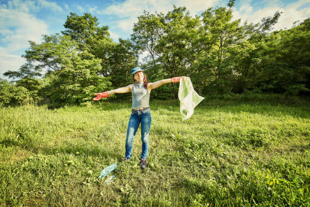 Young  girl picking up the garbage and putting it in a garbage bag on a natural background. stock photo