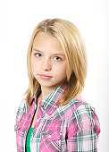 Young preteen girl with serious expression over white in studio.