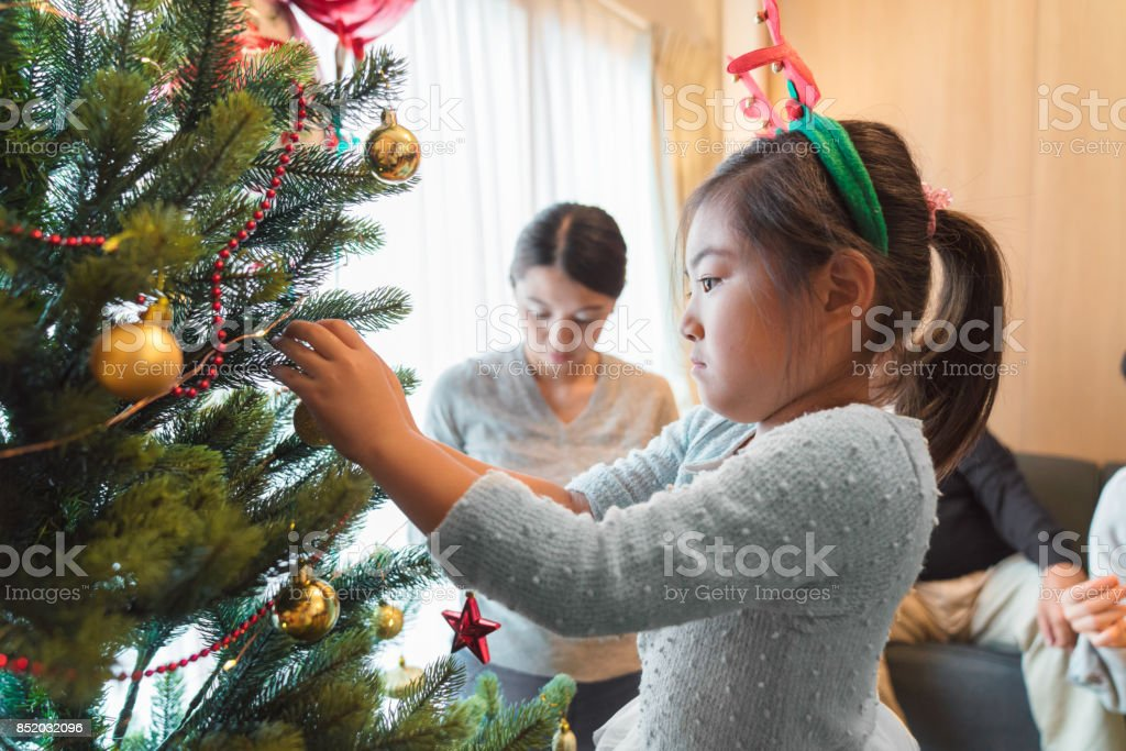 Japanese Christmas Tree Ornaments.Young Girl Placing Ornaments On A Christmas Tree Stock Photo