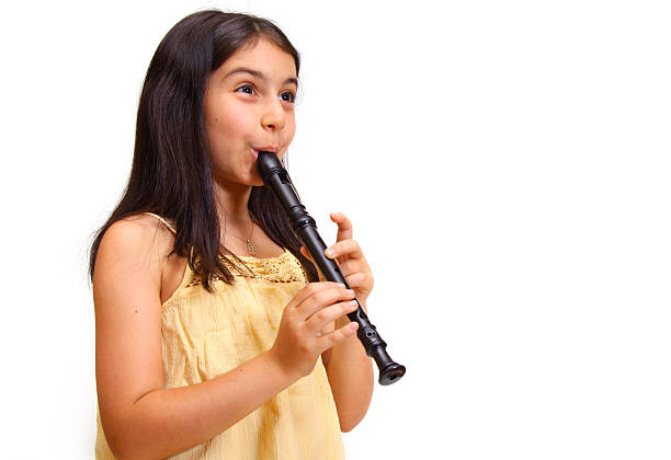 a young girl playing a black recorder - recorder stock photos and pictures