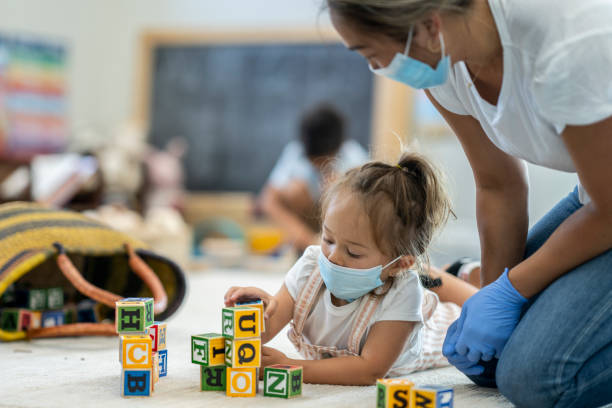 Young girl playing at daycare wearing a protective mask stock photo