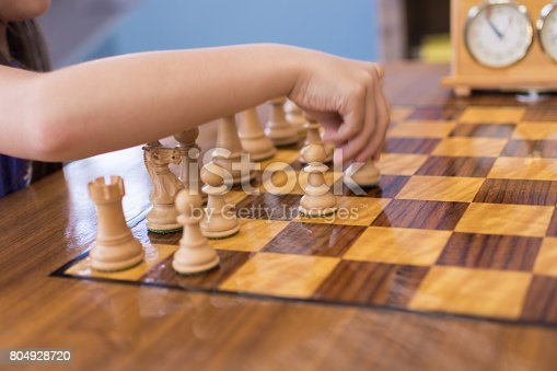 A 7 year old girl is playing chess and is moving her pieces in a high-speed fashion. A chess clock can be seen in the background of the chessboard, reinforcing the concept of speed and time.