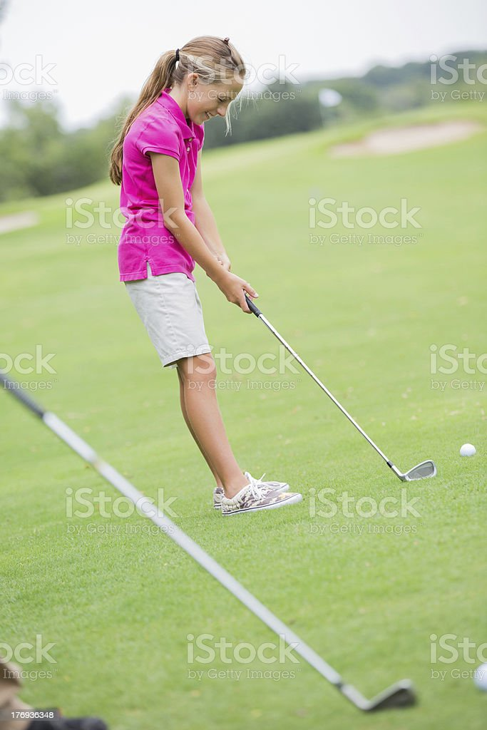 Young girl playing golf on green course royalty-free stock photo
