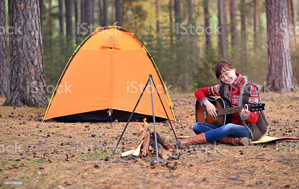 Young girl playing guitar in forest stock photo