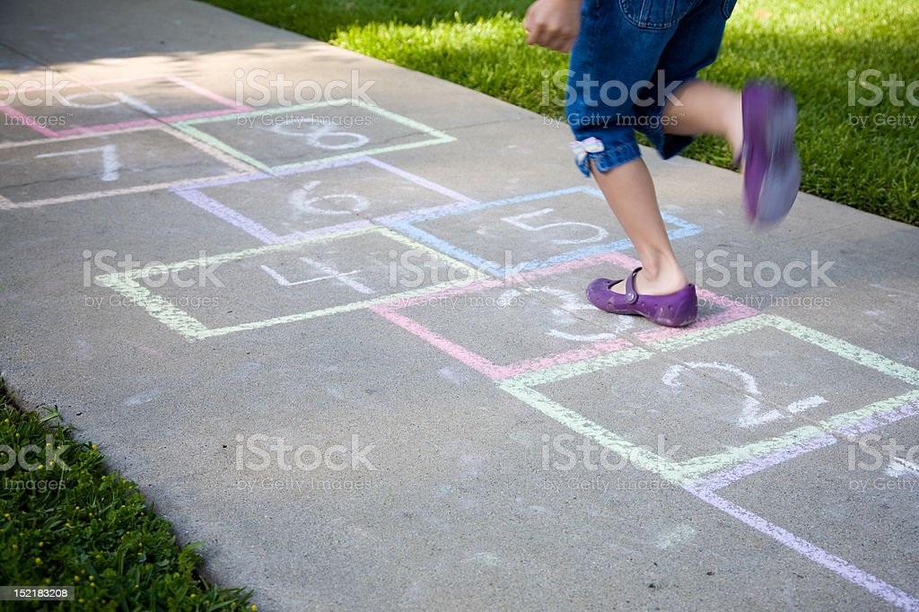 A young girl playing hopscotch on a sidewalk stock photo