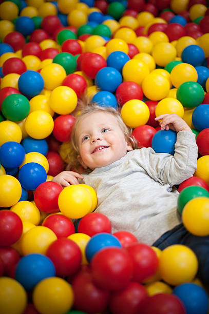 Young girl playing in a ball pool stock photo