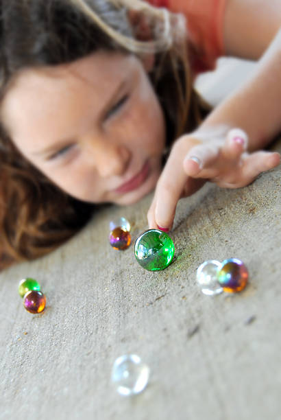 Young girl playing marbles stock photo