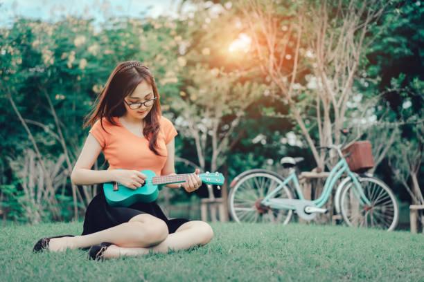 junge mädchen spielen, musik, rhythmus, melodie üben mit ukulele pastell sitzen auf dem rasen spaß oder ruhe und entspannung mit dem fahrrad vintage im park im freien - ukulele songs stock-fotos und bilder