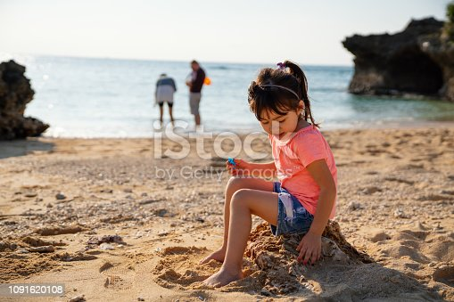 Young girl playing on a beach while on vacation with her family in the background