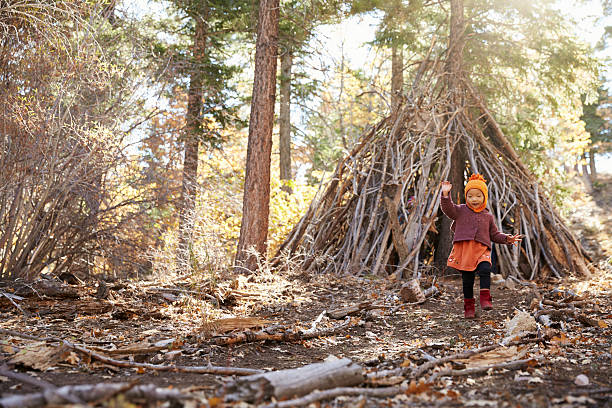 Young girl playing outside hut made of branches in stock photo
