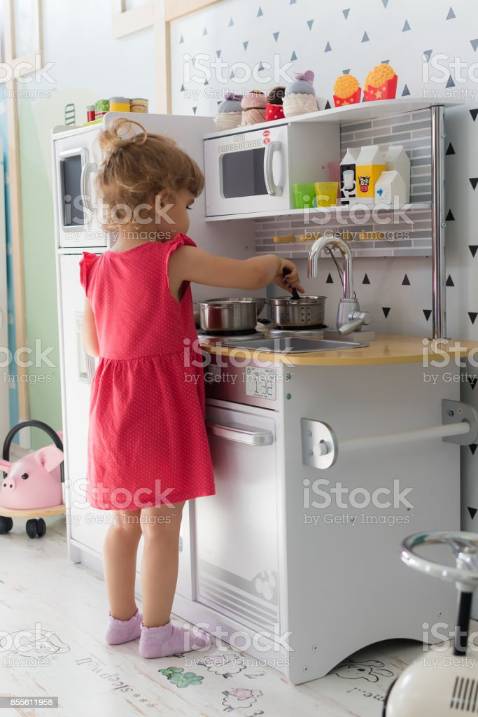 Young girl playing role in kitchen stock photo