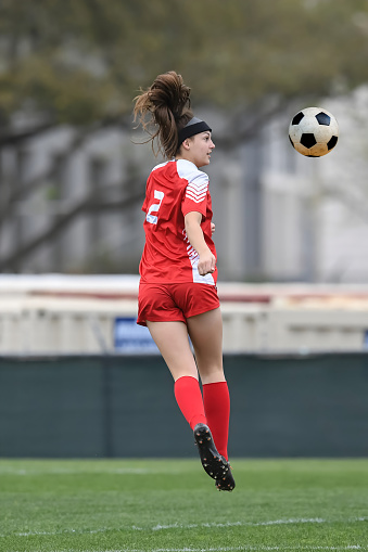 High school girl in red uniform playing in a soccer game.