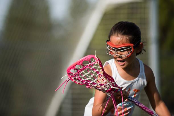 young girl playing sports outside - lacrosse zdjęcia i obrazy z banku zdjęć